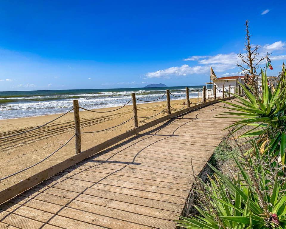 Una passerella in legno costeggia tutta la spiaggia di Lago Lungo. Oltre a condurre ai vari lidi e ristoranti, permette di fare una piacevole passeggiata con vista mare.