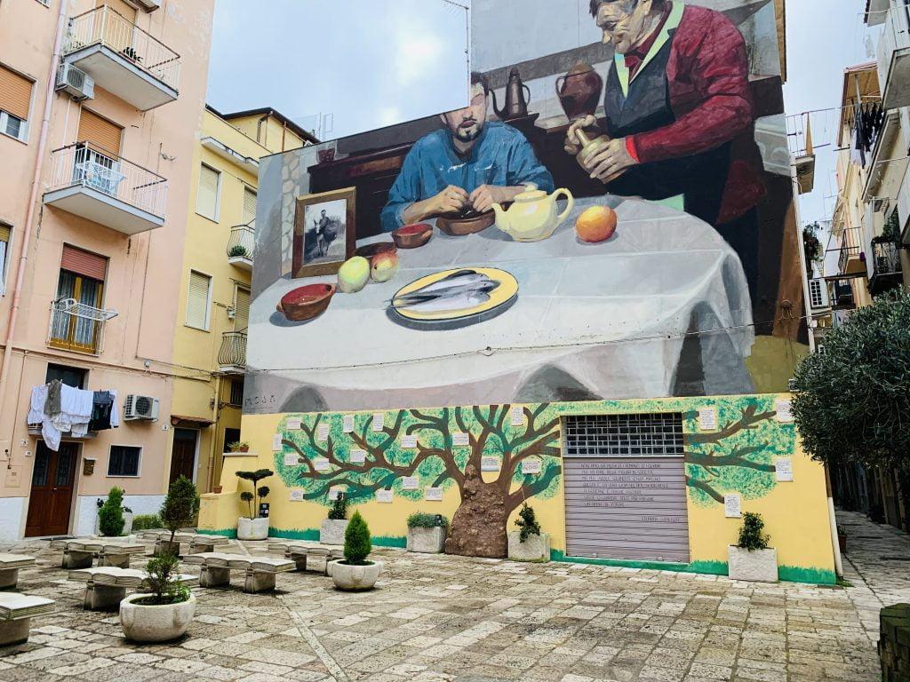 In Piazza Goliarda Sapienza a Gaeta troneggia il colorato murales che riproduce attimi di vita vissuta nel borgo, sotto il quale è stata creata la parete della poesia.